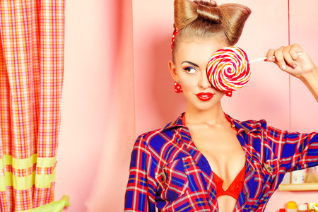 hair bow: Pretty pin-up girl posing on a pink kitchen with a lollipop. Retro style. Fashion.