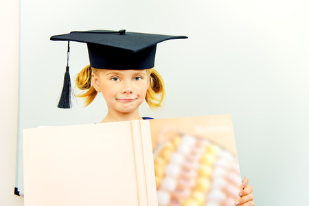 Cute little student girl in academic hat stands with a large open book. Educational concept. photo