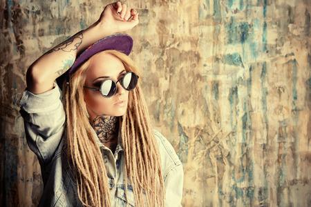 modern generation: Adolescente moderna con rastas rubias sobre el fondo del grunge. Estilo de los pantalones vaqueros. Generaci�n moderna.