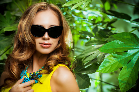 Attractive young woman among the tropical plants photo