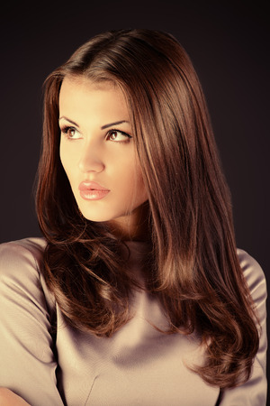 femme fatale: Beautiful fashionable model posing at studio in elegant long hair. Stock Photo