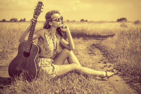 Romantic girl traveling with her guitar photo