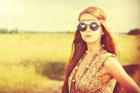 Romantic hippie girl standing in a field