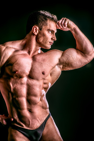 Handsome muscular bodybuilder posing over black background. photo