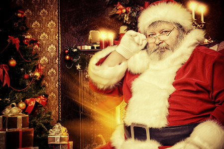 Portrait of smiling Santa Claus in a room decorated for Christmas.  photo