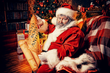 Santa Claus sitting in a room decorated for Christmas, and carefully read the list of good boys and girls photo