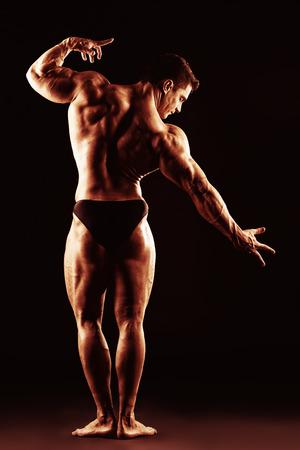Beautiful muscular man bodybuilder posing back over dark background photo