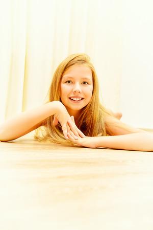 Cute joyful girl lying on a floor at home. photo