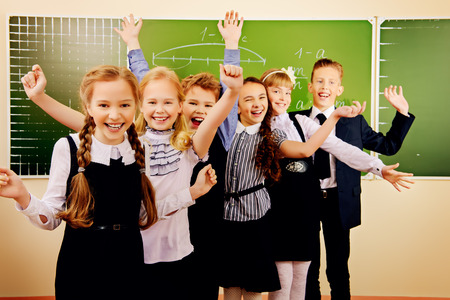 uniforms: Happy schoolchildren at a classroom. Education. Stock Photo