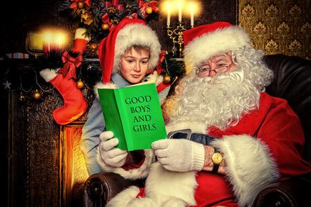 cor: Santa Claus and a cute boy reading a list of good boys and girls. Christmas home décor. Stock Photo