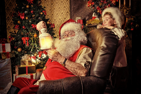cor: Santa Claus in his everyday clothes in Christmas home décor. Happy little boy helps Santa Claus get ready for Christmas.