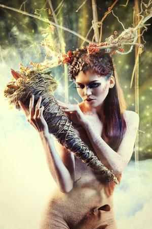 maquillaje de fantasia: Muchacha hermosa en la imagen de un ciervo salvaje se encuentra en un bosque desierto. Foto de archivo