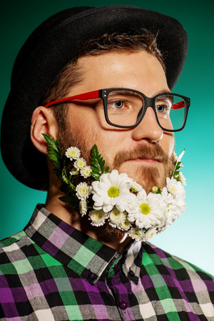 Funny young man with a beard of flowers wearing elegant bowler hat and glasses. photo