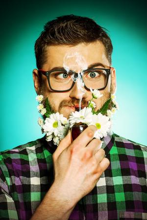 hombre fumando puro: Apuesto joven en gafas y barba de flores fumando una pipa.