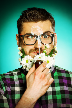 Handsome young man in glasses and a beard of flowers smoking a pipe. photo