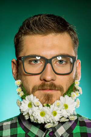 Handsome smiling young man in glasses and a beard of flowers. photo