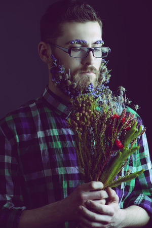 Handsome young man in spectacles and a beard of flowers. Black background. photo