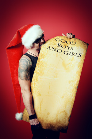 the tempter: Handsome brutal man in Christmas hat holding a list of good boys and girls. Over red background.