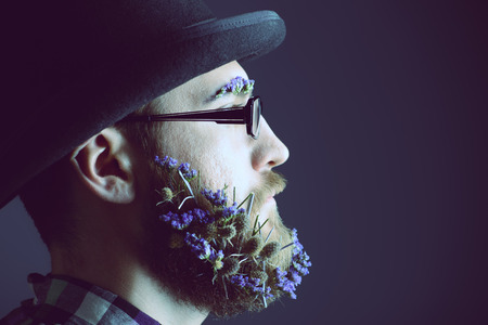 Handsome man with a beard of flowers wearing elegant bowler hat and glasses. Profile portrait. photo