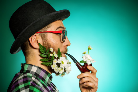 Extravagant man with a beard of flowers wearing elegant bowler hat and smoking a pipe. photo