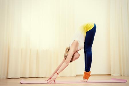 woman pose: Slender athletic girl doing yoga exercises indoor. Stretching. Stock Photo