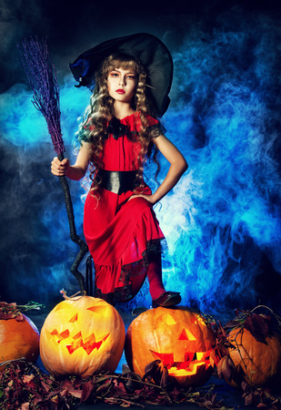 Little girl in a costume of witch posing with pumpkins over dark background. photo