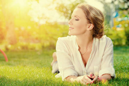 enjoy: Beautiful smiling woman lying on a grass outdoor. She is absolutely happy.