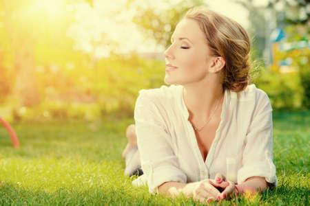 Hermosa mujer sonriente acostado en una hierba al aire libre. Ella es absolutamente feliz. Foto de archivo