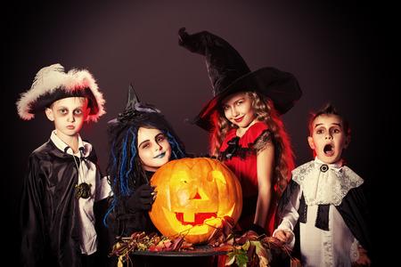 Fröhliche Kinder in Halloween-Kostümen posiert mit Kürbis über dunklen Hintergrund.