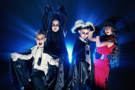 Cheerful children in halloween costumes posing over dark background. photo