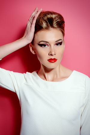 Fashion shot of a stunning young woman posing in white dress over pink background. Bright makeup. Beauty, fashion. photo