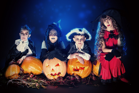 kid smiling: Cheerful children in halloween costumes posing with pumpkin over dark background.