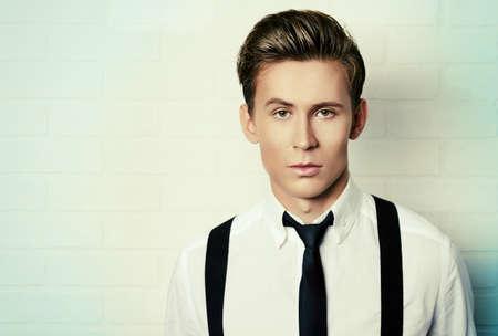 modelos masculinos: Retrato de un apuesto joven en la camisa blanca andblack empate por la pared de ladrillo blanco. Negocio.