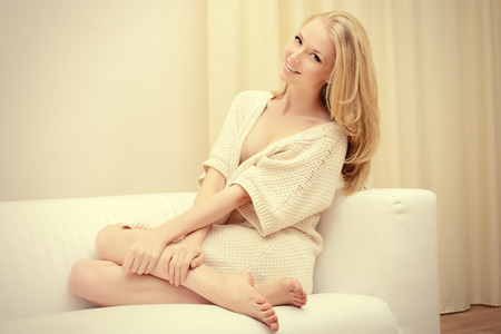 Pretty young woman sitting on a sofa at home and smiles. Interior.
