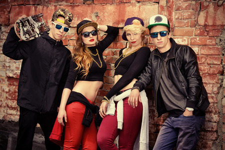 Group of young modern people posing together with fun. Urban lifestyle. Hip-hop generation. photo