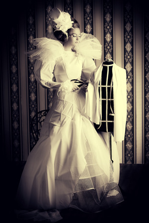haute couture: Beautiful fashion model in the refined white dress and mannequin. Vintage style. Art project. Haute Couture.
