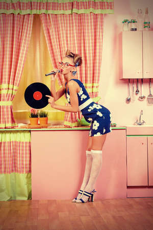 Beautiful sexy pin-up girl singing with microphone and vinyl record on a pink kitchen. Retro style. Fashion. photo