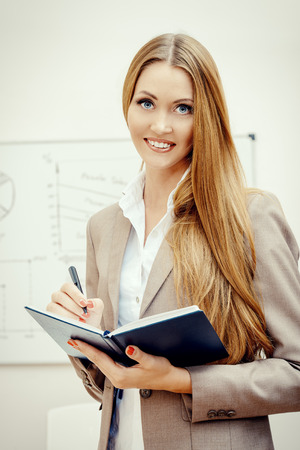 Business woman standing at the office with opened diary and smiling at camera. photo