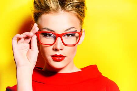 labios rojos: Close-up retrato de un modelo de mujer impresionante en vestido rojo y gafas elegantes que presentan sobre el amarillo. Belleza, la moda, la óptica. Foto de archivo