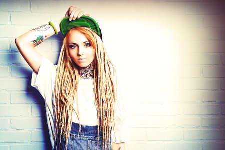 modern generation: Adolescente moderna con rastas rubias de pie junto a la pared de ladrillo. Estilo Jeans. Generaci�n moderna.