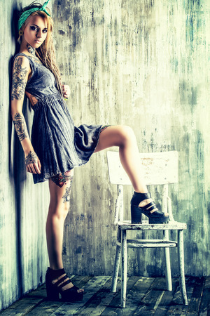 Sexual blonde girl with fascinating dreadlocks posing by the grunge wall. Pin-up style. photo