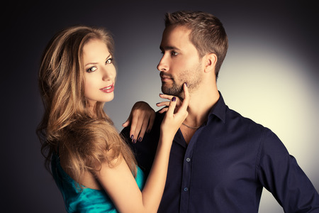sexual couple: Portrait of a beautiful young couple in love posing at studio over dark background.