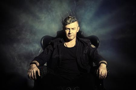 trono: Retrato de un hombre guapo masculino en elegante traje negro sentado en una silla en un estilo clásico de la vendimia. Foto de archivo