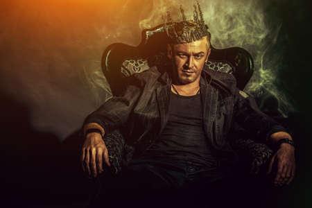 corona rey: Retrato de un hombre guapo masculino en un elegante traje negro, sentado en una silla en un estilo clásico de la vendimia.