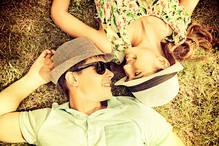 emotional couple: Happy young couple relaxing on the lawn in a summer park. Love concept. Vacation. Stock Photo