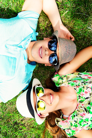 young lovers: Happy young couple relaxing on the lawn in a summer park. Love concept. Vacation. Stock Photo