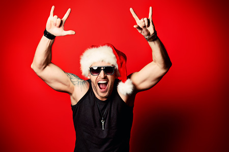 celebration party: Portrait of a happy handsome brutal man in Christmas hat. Over red background. Stock Photo