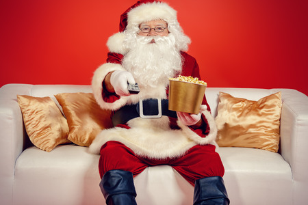Traditional Santa Claus sitting on the couch watching TV, eating popcorn and drinking soda. Christmas.