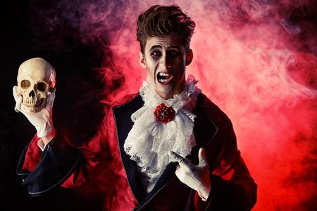 dracula: Comic vampire holding a skull. Halloween. Dracula costume.