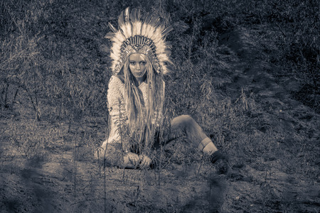 chieftain: Fashion shot of a beautiful girl in style of the American Indians. Western style. Jeans fashion. Toned photo. Stock Photo